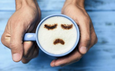 A pair of hands holding a mug of coffee with a sad face drawn in chocolate