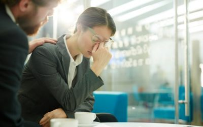 bereaved employee with head in hands being comforted by colleague