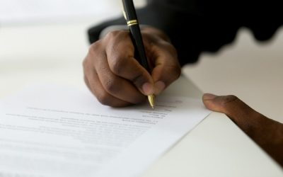 Close up of hands of employee signing an employment contract
