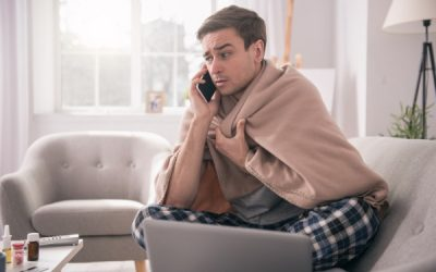 young man at home on sofa calling into work sick