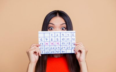 Woman holding up calendar with days crossed off