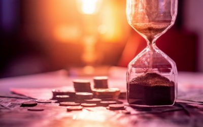 An hourglass sits on a table beside a pile of coins