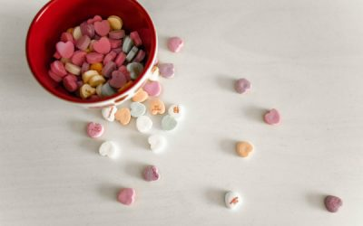 A bowl of heart-shaped sweets spilling over the table